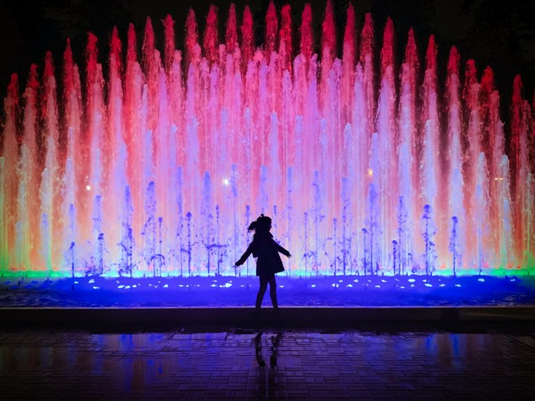 silhouette of person standing near water fountain